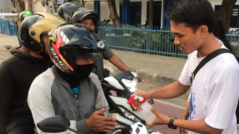 Kader GMKI Cabang Medan semprotkan cairan pembersih tangan kepada pengendara. Foto: Istimewa