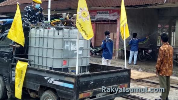 Anggota DPD AMPI Paluta saat menyemprot disinfektan di rumah warga di Gunung Tua. Foto: Rakyatsumut.com/ Rifai Dalimunthe.