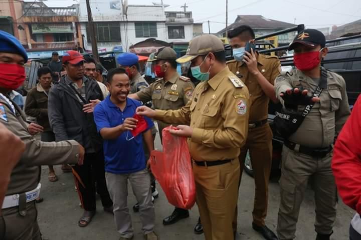 Bupati Taput, Nikson Nababan saat membagikan masker kepada masyarakat. Foto: istimewa