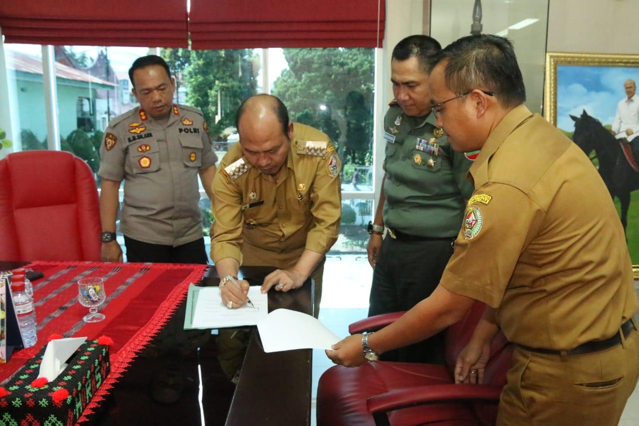 Bupati Taput Nikson Nababan menandatangani hasil Rakor yang memutuskan Lokcdown terkait antisipasi penyebaran Covid-19. Foto: Istimewa