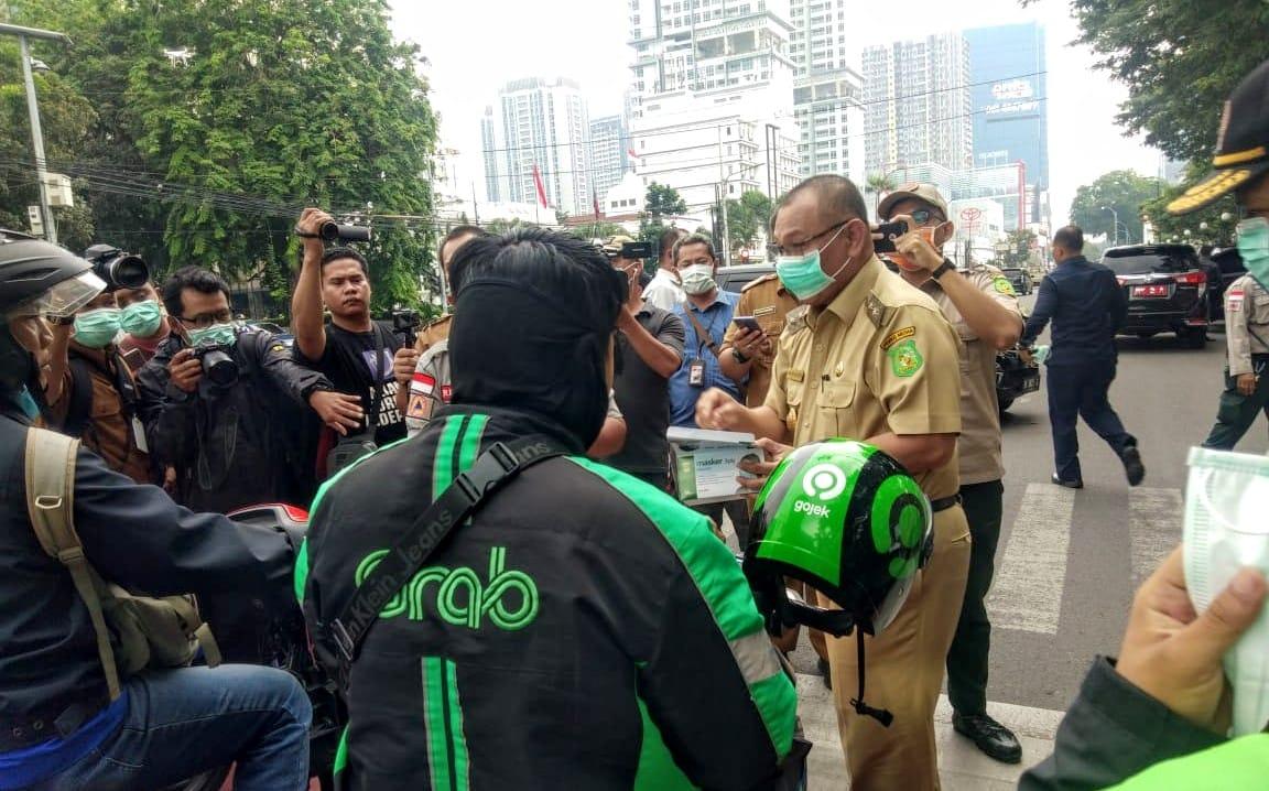 Teks: Pelaksana tugas Wali Kota Medan Akhyar Nasution membagikan masker kepada warga pengguna jalan raya di Kesawan Medan. Foto: Rakyatsumut.com / Ucis