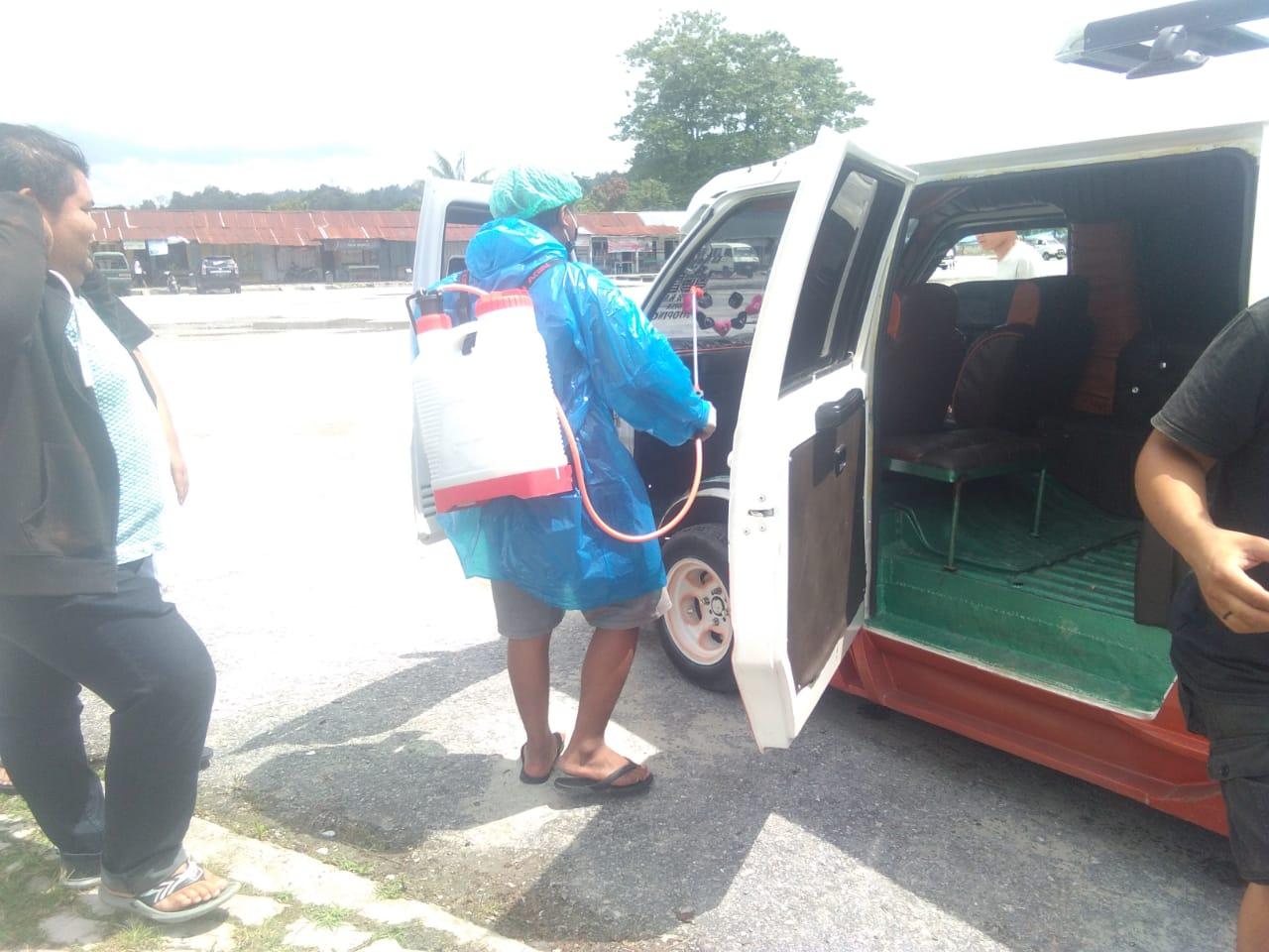 Anggota IAT saat menyemprot angkutan umum menggunakan cairan desinfektan. Foto: Rakyatsumut.com/ Paska Marbun