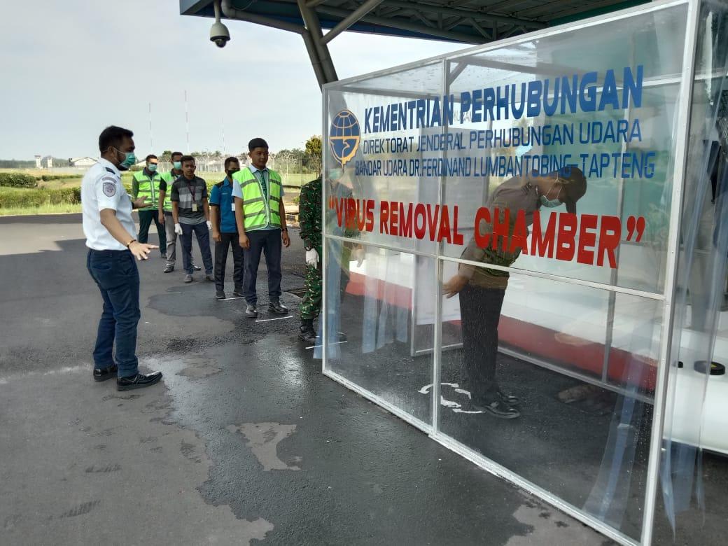 Petugas Bandara DR FL Tobing, Pinangsori, saat mengarahkan para penumpang yang mendarat untuk melintasi bilik Virus Removal Chamber. Foto: Istimewa