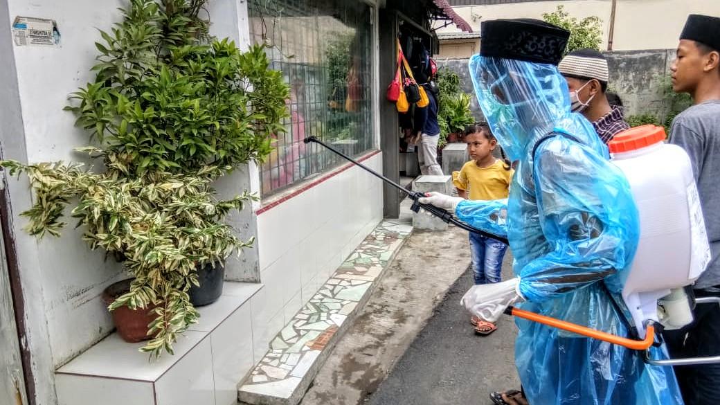 Remaja Masjid Al Jihad Sari Rejo Medan Polonia semprot rumah warga dengan cairan disinfektan. Foto: Istimewa