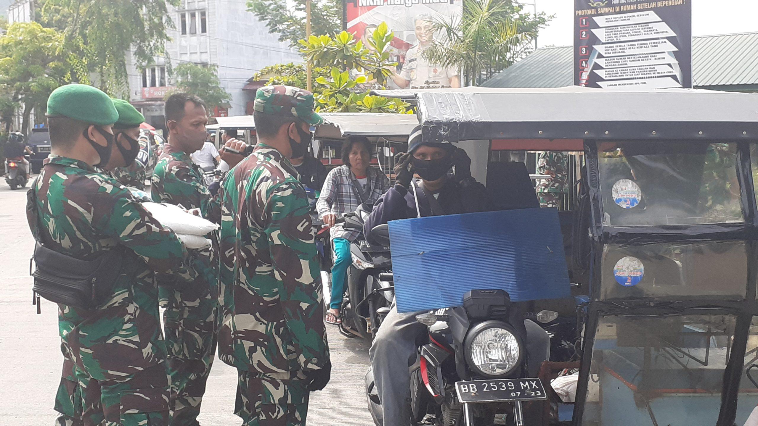 Personel Ķorem 023 Kawal Samudera saat membagikan sembako dan masker kepada abang becak. Foto: Rakyatsumut.com/ Mirwan Tanjung