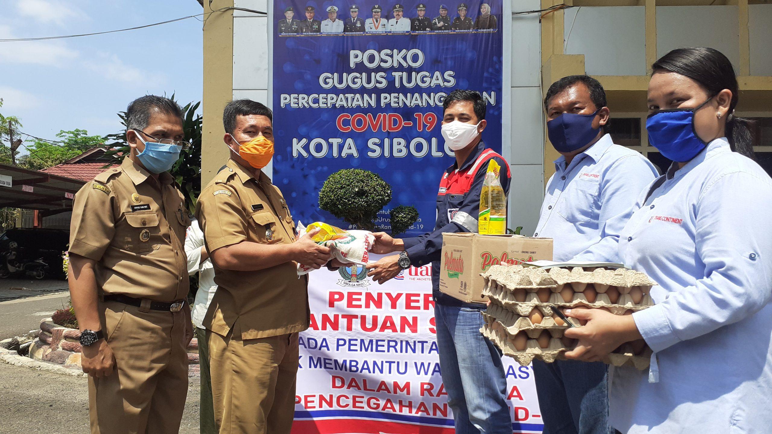 Sekretaris Gugus Tugas Percepatan Penaganan Covid-19 Kota Sibolga Juangon Daulay saat menerima bantuan yang diserahkan Kordinator Transcontinent Cabang Sibolga Hadi Tanjung. Foto: istimewa
