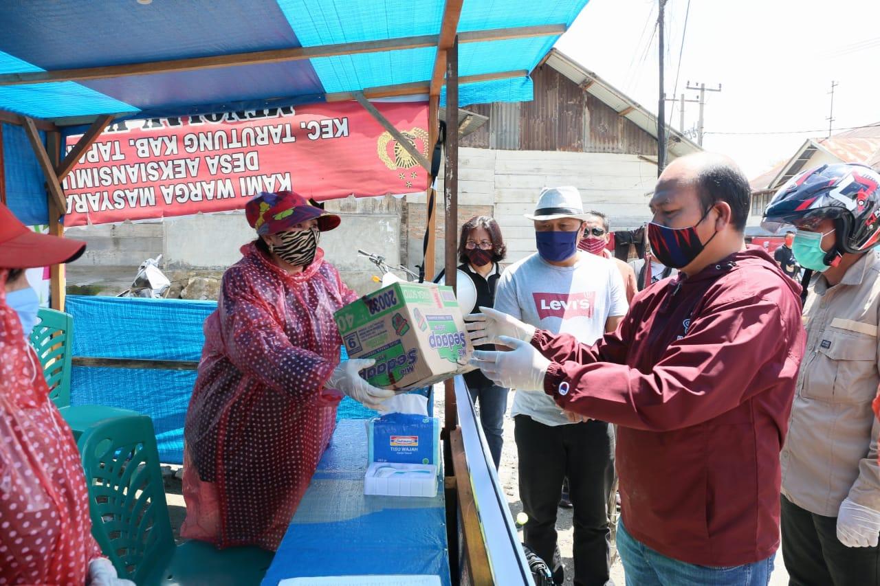 Nikson Nababan membagikan bantuan logistik kepada relawan posko di Kecamatan Tarutung. Foto: Istimewa
