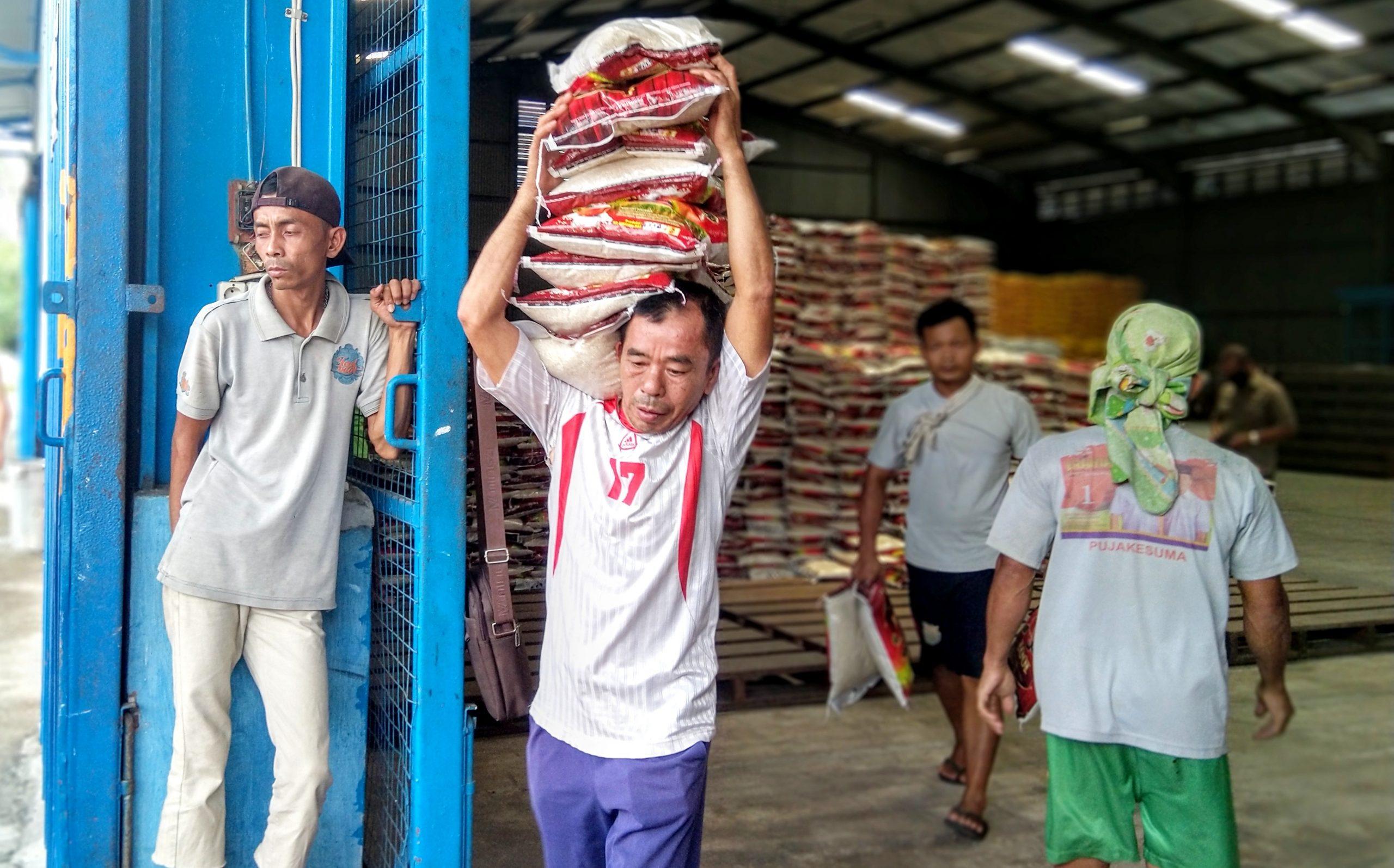 Pekerja sedang mengangkat beras bantuan untuk masyarakat yang terkena dampak Covid-19, dari Gudang Bulog Pulo Brayan Darat I Medan. Foto: Rakyatsumut.com / Ucis
