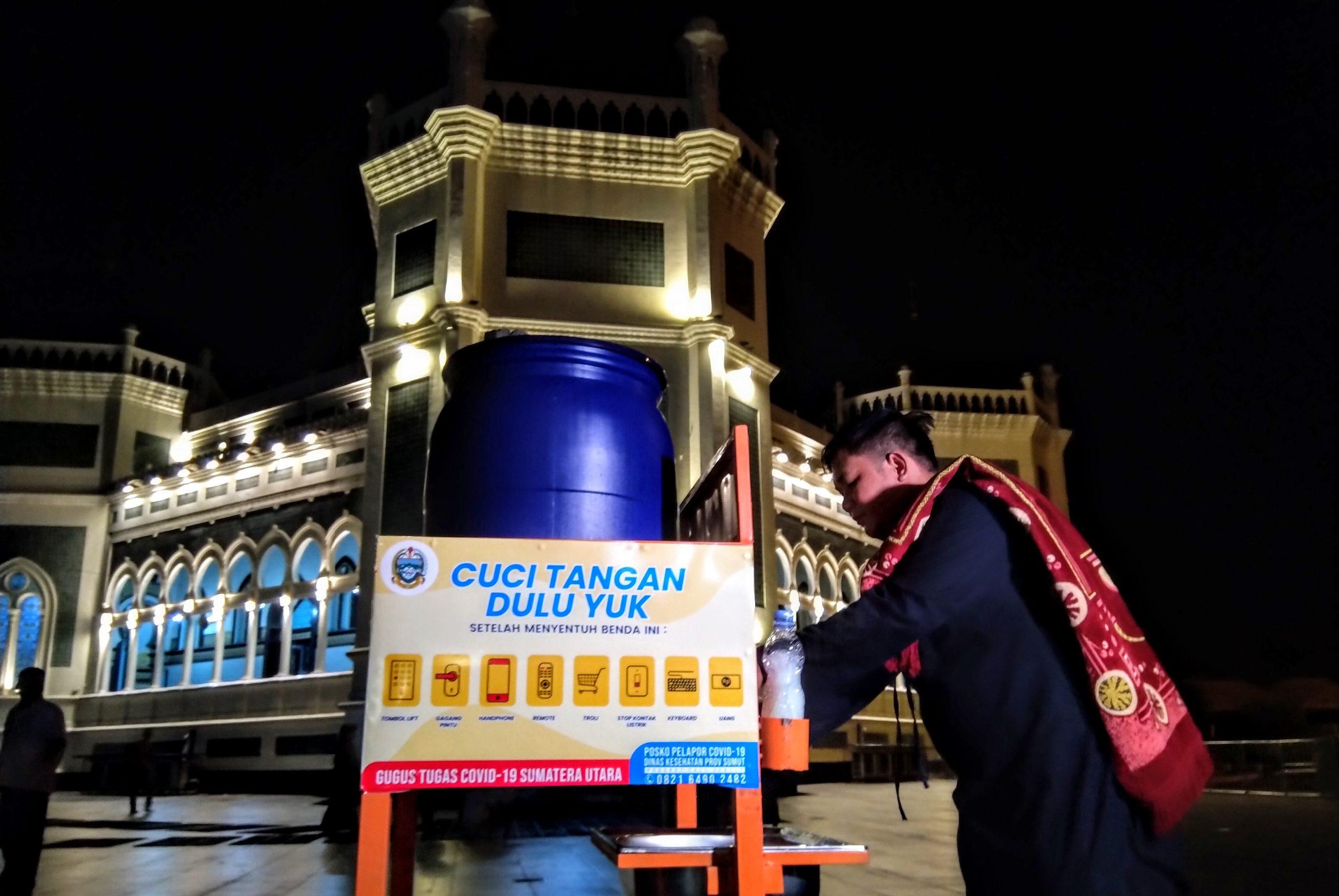Seorang warga mencuci tangan sebelum pelaksanaan Salat Tarawih di Masjid Raya Al Mashun Medan. Foto: Rakyatsumut.com/Muklis