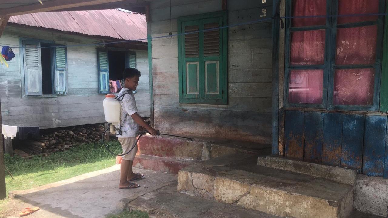 Seorang anggota NNB Desa Sidingkat, Kecamatan Padang Bolak, menyemprotkan cairan disinfektan ke rumah warga. Foto: Rakyatsumut.com/ Rifai Dalimunthe