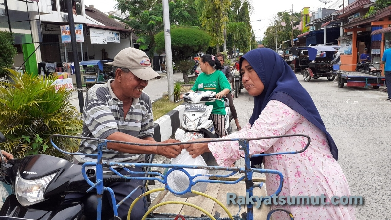Hasminah saat menyerahkan paket bantuan yang ia terima ke seorang bapak pengendara becak barang yang sedang melintas. Foto: Rakyatsumut.com/ Mirwan Tanjung