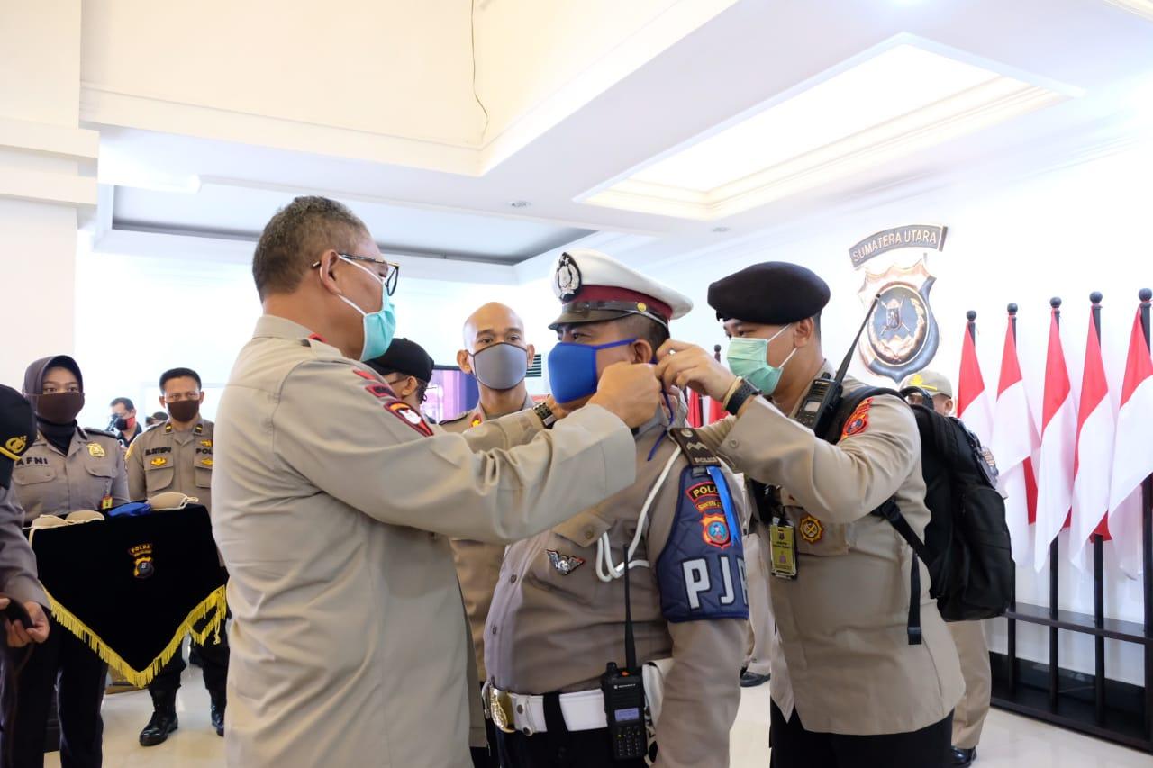 Kapolda Sumut Irjen Pol Martuani Sormin saat memasangkan masker ke seorang personil Polda Sumut. Foto: Istimewa