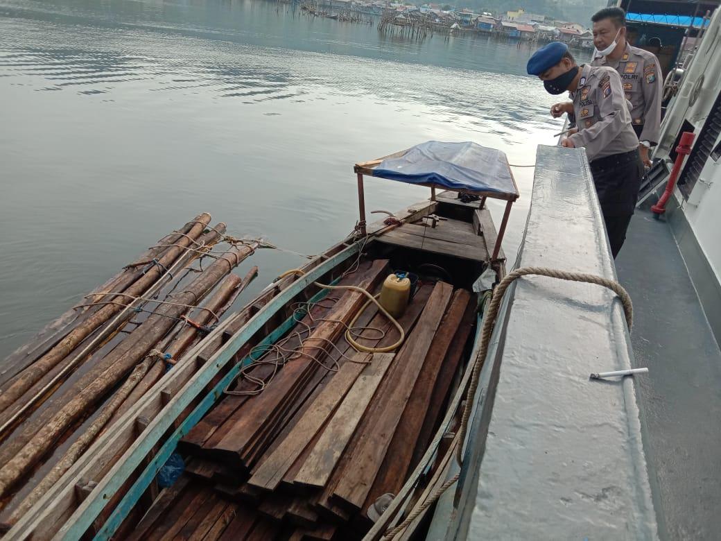 Dua orang personel Satpol Air Polres Sibolga saat memeriksa puluhan batang kayu illegal yang diamankan. Foto: Istimewa