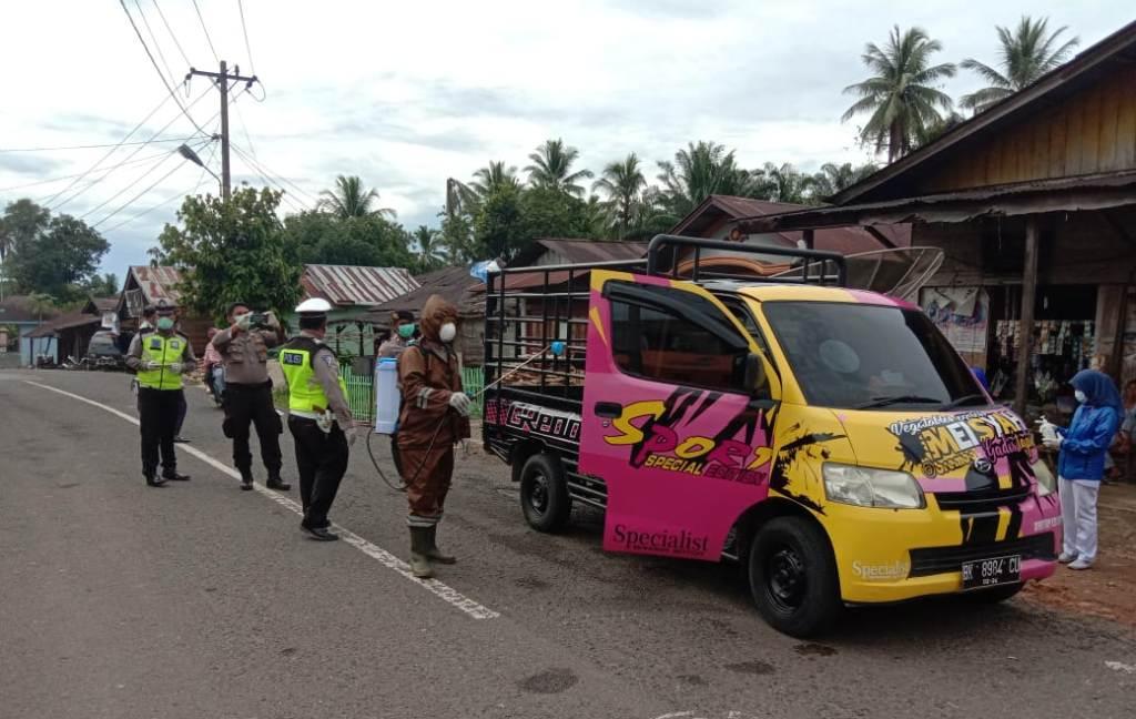 Personel gabungan dari Forkopimka Kecamatan Sibabangun saat menyetop satu kendaraan roda empat di Desa Angoli, Minggu (5/4/2020). Kendaraan itu disemprot disinfektan dan para penumpangnya diukur suhu tubuh oleh petugas medis. Ini dilakukan sebagai pengawasan dan penjagaan di perbatasan daerah itu, pasca PDP asal Kota Padangsidimpuan meninggal. Foto: Istimewa