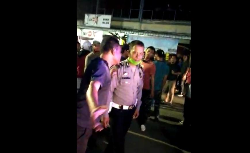 Kepala Urusan Binaan Organisasi (KBO) Sat Lantas Polres Samosir S. Sagala (mengenakan seragam) saat mengamankan kerumunan warga. Foto: Tangkapan layar