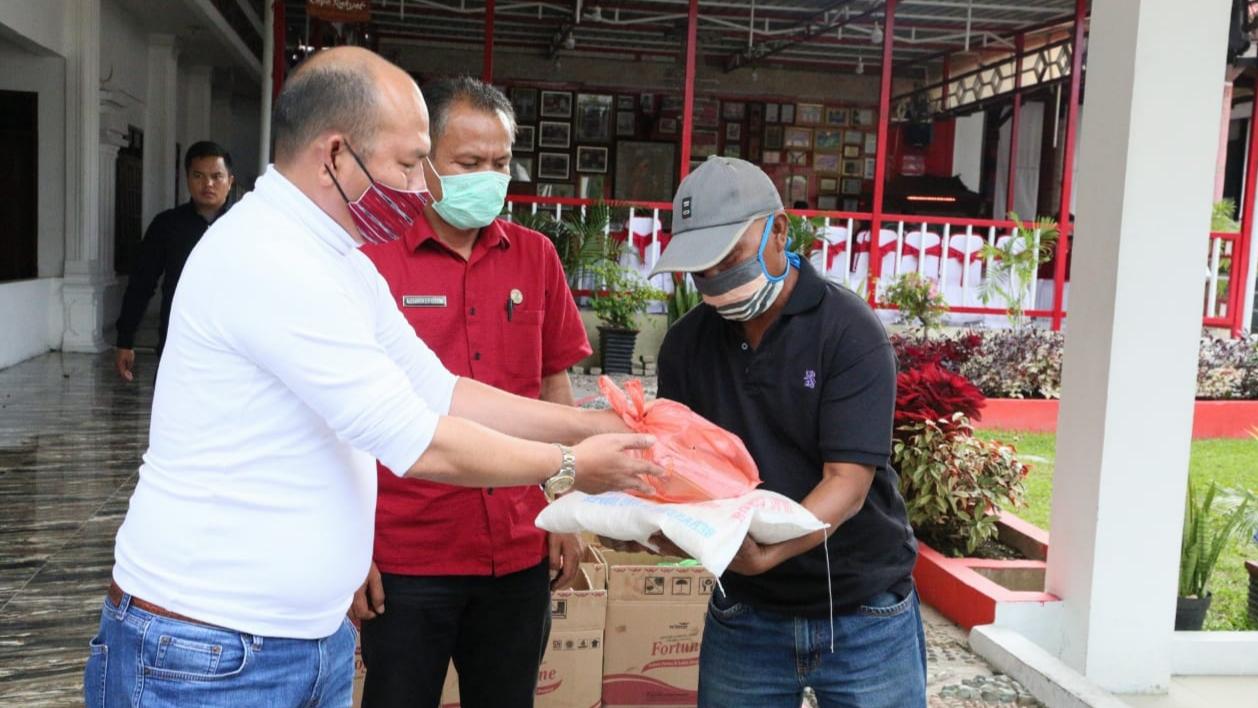 Bupati Taput Nikson Nababan menyerahkan bantuan paket sembako ke perwakilan pekerja terdampak covid-19. Foto: Istimewa