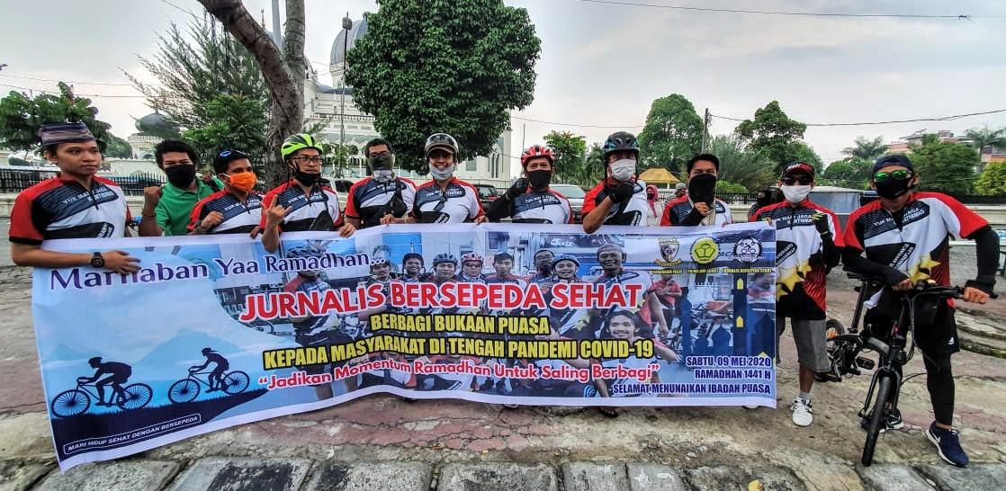 Jurnalis Bersepeda Medan gowes sambil bagikan ratusan paket sembako kepada warga. Foto: Istimewa