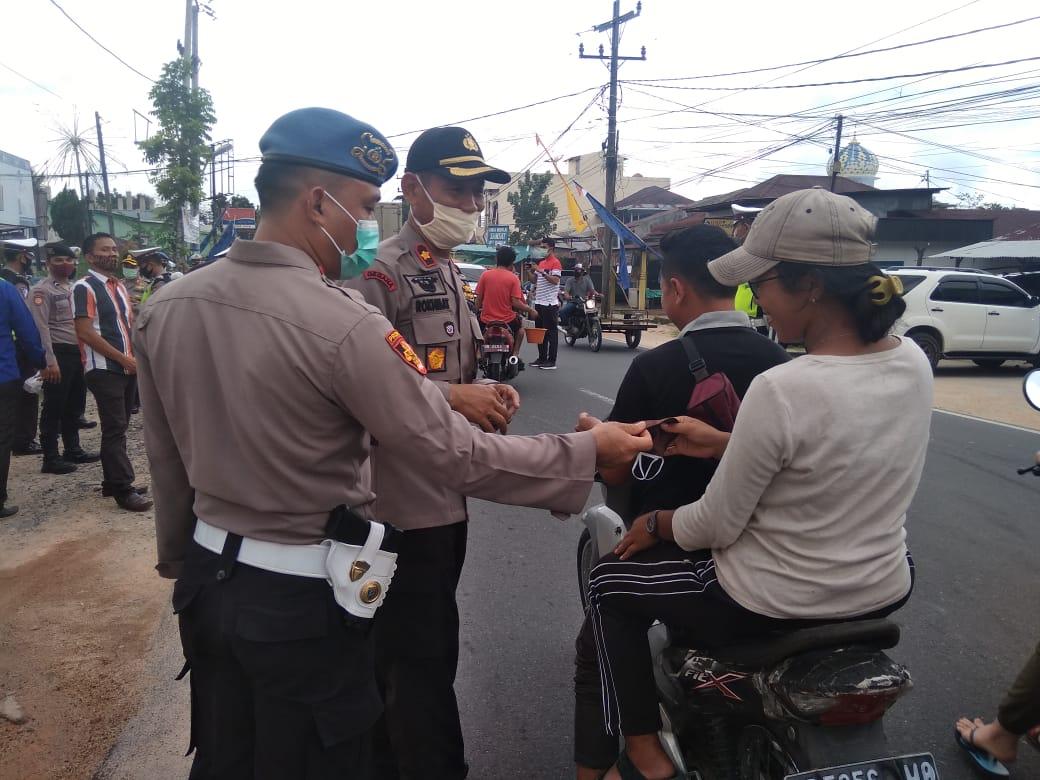 Wakapolres Tapteng saat bagi-bagi masker dan takjil kepada masyarakat yang melintasi pos pengamanan Polres Tapteng. Foto: istimewa