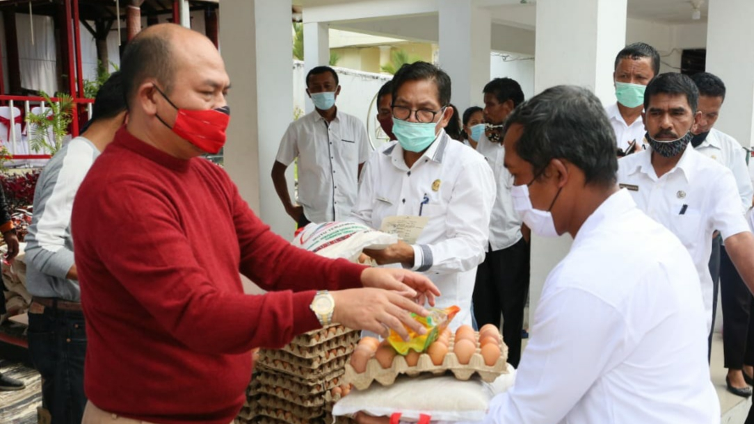 Bupati Taput Nikson Nababan saat menyerahkan secara simbolik bantuan pangan kepada tenaga honorer. Foto: Istimewa