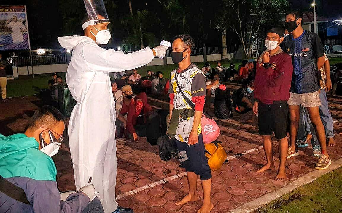Personel TNI AL melakukan pemeriksaan suhu tubuh terhadap ratusan TKI Ilegal dari Malaysia yang diamankan di perairan Kabupaten Labuhan Batu Utara. Foto: Istimewa