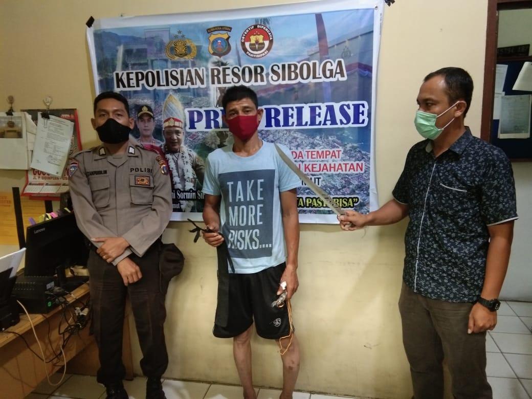 Tersangka bersama parang yang digunakan membacok abangnya saat diamankan di Polres Kota Sibolga. Foto: istimewa