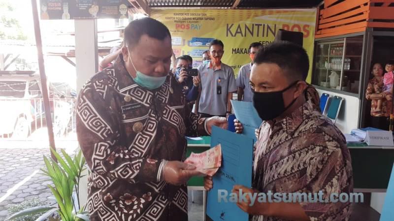 Wali Kota Sibolga M Syarfi Hutauruk menyerahkan BST secara simbolis kepada seorang penerima. Foto: Rakyatsumut.com/ Mirwan Tanjung