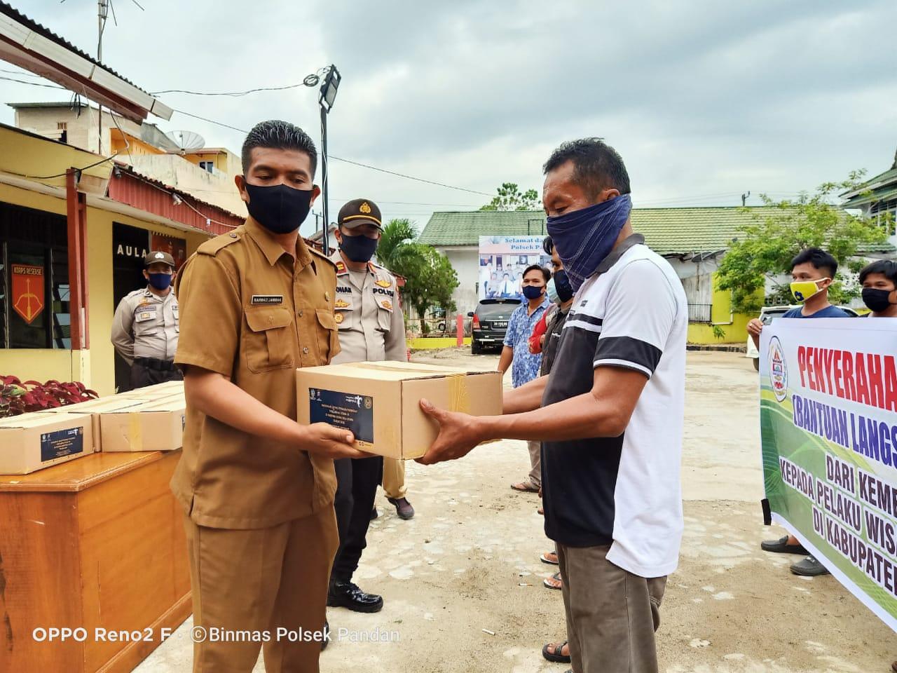 Kadis Pariwisata, Rahmad Jambak bersama personil Polres Tapteng saat menyerahkan sembako kepada pekerja kapal. Foto: istimewa