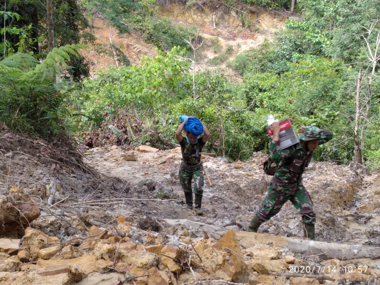 Personil TNI TMMD saat memikul bahan material. Foto: istimewa