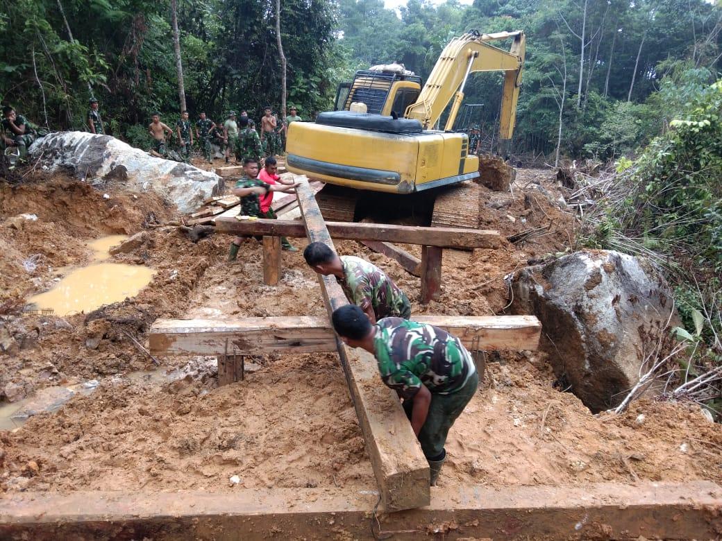 Personil satgas TMMD ke 108 Kodim 0211/TT dan alat berat saat membangun jembatan. Foto: istimewa