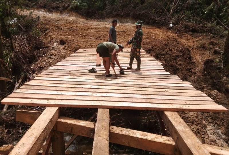 Personel Satgas TMMD saat merehab jembatan rusak di Desa Siantar CA. Foto: Istimewa