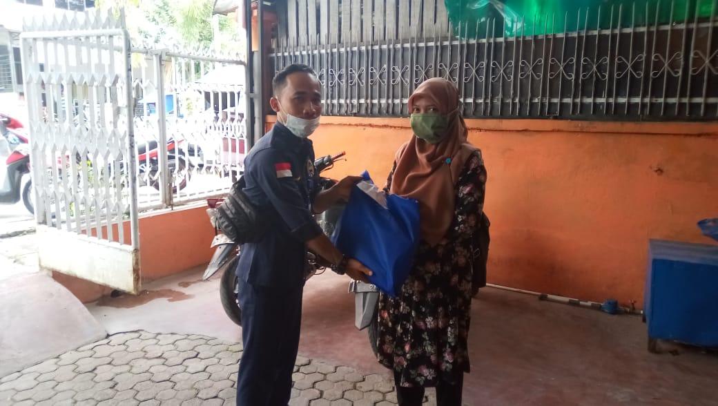 Salah satu tenaga ahli Anggota DPR RI Delmeria Sikumbang, Firmansyah saat menyerahkan bantuan di Kelurahan Pasar Belakang. Foto: istimewa