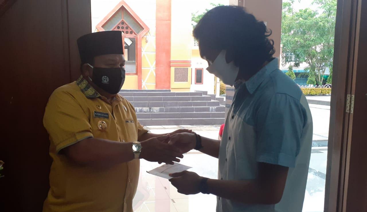 Wali Kota Sibolga saat menyerahkan beasiswa kepada Mahasiswa Universitas Sumatera Utara. Foto: Rakyatsumut.com/ Mirwan Tanjung