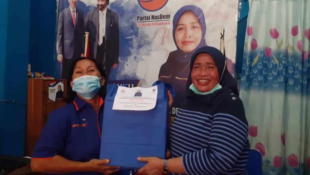 Delmeria Sikumbang saat menyerahkan bantuan hadiah natal kepada kader Partai NasDem Kota Sibolaga. Foto: Rakyatsumut.com.