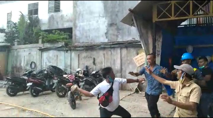 Eduar Lumbangaol selaku humas proyek yang mengambil batu dan melemparkannya kepada Amin Jemayol. Foto: tangkaplayar